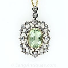 A gorgeous 5.15 carat light yellowish green beryl (the same material as emerald, but a lighter hue) is framed by an openwork scroll motif se...