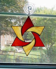 This stained glass star suncatcher is made with alternating orange and yellow swirled corsica glass and orange red swirled opalescent glass.