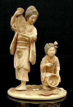 A Japanese carved ivory okimono Meiji period 1868 - 1912, the figure group depicting a mother and daughter inspecting their catch of two flounder the young girl holding a basket with mollusks signed lacquer plaque to base with engraved flower motif 18 cm high.