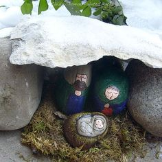 Painted rocks nativity set nestled in a snow-covered rock cave