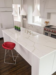 A trio of contemporary white pendant lights hang over a Calacatta Borghini quartz-topped island. A dark quarter-sawn oak floor provides contrast to the gray and white color palette. A cherry red leather bar chair pops against the bright background. The red is repeated on the stove knobs for an extra pop in intrigue.