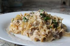 Slow Cooker Stroganoff Recipe Main Dishes with stew meat, onions, beef broth, cream of mushroom soup, cream cheese, worcestershire sauce, garlic powder, egg noodles, chopped parsley, extra-virgin olive oil, salt, pepper