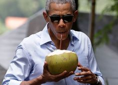 President Barack Obama drinks from a fresh coconut along the banks of…
