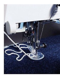 BERNINA FREE MOTION COUCHING FOOT This presser foot allows you to feed cords, ribbons and braid directly under the needle, so that lines and shapes of any sort can be precisely guided and sewn on.