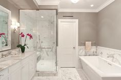 This transitional gray bathroom features gorgeous white marble throughout that makes the space feel bright and luxurious.