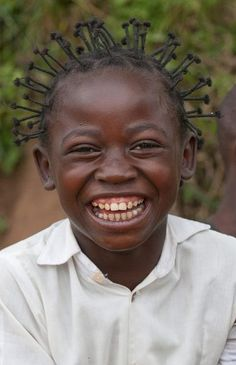 A young girl greets visitors in Kamina, Democratic Republic of Congo.