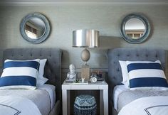 Blue and gray boys' bedroom features light gray grasscloth on upper wall and gray board and batten trim on lower wall lined with blue distressed mirrors and gray velvet tufted sleigh headboards on twin beds dressed in blue awning stripe pillows flanking a white West Elm Parsons Mini Desk.