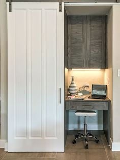 Small kitchen desk hidden behind barn door. Desk in EVRGRN Rok, a light gray engineered wood with 3 piece cabinet doors and drawer front