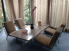 outro conjunto de cadeiras em ferro e mesa com mosaicos que ornamentam a sala