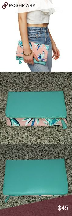 "Rachel Pally Reversible Clutch or Pouch NWT gorgeous large clutch or pouch, big enough to hold your everyday essentials! It could also be used as a travel bag for makeup or jewelry! Fold it over to use it as a clutch, with either side facing outward.  Coral and mint colored with a tropical print, this bag is beautiful, eye-catching, and in style! Zipper closure, khaki inside, one pocket on the inside, and a cute mint tassel on the zipper pull. 💖  This trendy bag measures 10.25"" wide and 12""…"