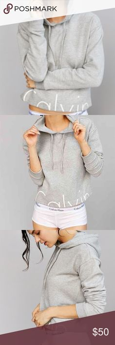"""Calvin Klein Pullover Cropped Hoodie Made from soft fleece, the MyCalvins Cropped Pullover Hoodie has a modern, feminine fit. Other details include a drawcord hood, ribbed cuffs, and an updated graphic at the hem.  Pullover hoodie Graphic at the hem Cropped cut Soft feel Drawcord at the hood Model is wearing a small Model's measurements: Height: 5'10"""" Bust: 34"""" Waist: 24"""" Hips: 34"""" 60% cotton, 40% polyester Machine washable Calvin Klein Tops Sweatshirts & Hoodies"""