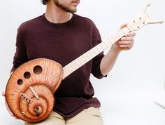 This is just plain awesome. An electric, long neck (look at the tuning head!) snail body ukelele.