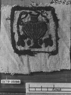 Place of origin: Akhmim, Egypt  Date:4th/5th century  Museum number:1379-1888  Square panel from a linen tunic (?), each embroidered in purple wool and undyed linen thread, with a gadrooned two-handled vase in which are two foliated stems.  See also 1380-1888.
