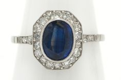 The Jackson classic Art Deco sapphire engagement ring with a bold, octagon halo detailed with milgrain galore. The enchanting, velvety, royal blue of this gem will make your heart melt. The sizable 1.66 carat oval in a low setting of platinum surrounded by chunky old cut diamonds is supported by a platinum band and pierced, open work under crown. #artdeco #bluesapphire #engagementring #engagementrings #artdecoring #artdecorings #bridalring #bridalrings #love #ido #engaged #platinum #sapphire Estate Engagement Ring, Antique Engagement Rings, Halo Diamond, Diamond Cuts, Jackson's Art, Art Deco Ring, Bridal Rings, Royal Blue, Sapphire