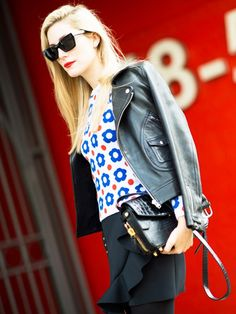 Joanna Hillman, style director at Harper's Bazaar wears a printed sweater, leather jacket, black skirt, Alexander Wang bag, and Céline sunglasses
