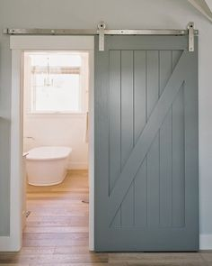 barn door bathrooms - gray painted half-buck wood slider on the hallway side of the bath - decorpad via atticmag