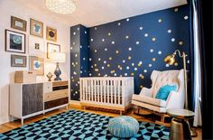 Gold and blue boy's nursery features an accent wall painted Benjamin Moore Hudson Bay lined with silver and gold dot wall decals, Land of Nod Lottie Dot Decals, lined with an Oeuf Classic Crib Birch, next to a West Elm Patchwork Dresser Multi, under a collection of art.