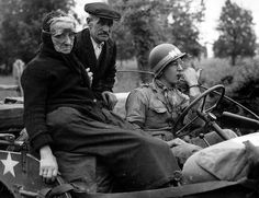 An elderly couple sitting in a jeep driven by an MP. The woman has a pair of protective eye goggles against gas attack. Normandy, 1944 ~
