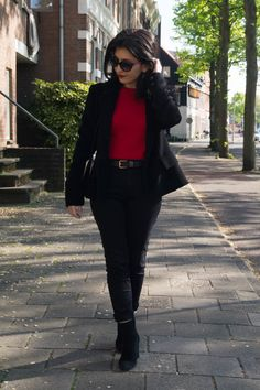 Red knitwear top with pearls, black blazer, black trousers, suede ankle boots, striped bag