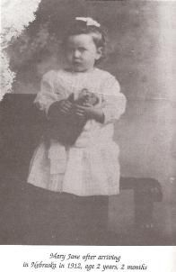 "Mary   Jane Baade, age 2 years, 2 months, came to Grand   Island on the orphan train to meet her new family.    Of the nine traveling west that summer of 1912, Mary   Jane was the ""littlest one of the whole bunch,"" she says.   She remembers bits of the journey. It was the first time   she had ever been outside.    Placed in a New York orphanage when she was two   weeks old she lived inside the walls of the Catholic   institution for the first 26 months of her life. The nuns   there stitched the"