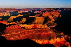 The Grand Canyon looks red and dramatic as the sun's angle moves up the sky.
