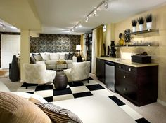 To set the scene for this Indian-inspired basement, Candice covers the walls in a black-and-gold paisley wallpaper and a metallic-backed sisal wallpaper. Black-and-white carpet tiles create a chic checkerboard across the room, while luxe fabrics on the furniture and window treatments add a glam factor.