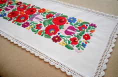 Hand-embroidered small tablecloth with crochetede edge.