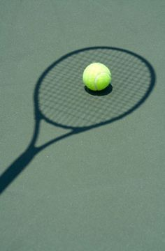 Awesome picture of a tennis ball and the shadow of a tennis racket!