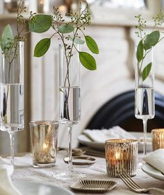 Give those underused Champagne flutes a temporary gig as bud vases. Fill each about halfway with water (it looks best if all the water lines match) and drop in two sprigs of lightweight greenery. Place alongside dinner plates to spruce up the whole table.