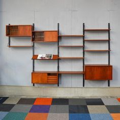 The wall unit is modular and can be rearranged as desired. It is made from teak with black lacquered metal.