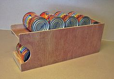 Can Dispenser. They are selling it, but pretty simple to make: 2 shelves, angled opposite (top angled down towards back, bottom angled down towards front) 'hole' near back of top shelf wide enough for 1 can. Have stopper on bottom so cans don't slide out. I guess put everything together with wood glue? Maybe put in a couple 'bracer' bars between top and bottom shelves to make it more stable. Make it yourself so you can have custom size for pasta sauce jars etc.