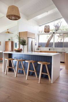 a bright and airy Cali kitchen with a navy blue breakfast bar