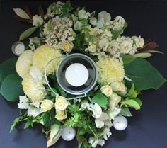 Table centre with blooms cream roses & tea lights.