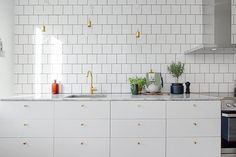 white kitchen, cabinet shape, brass accents, tile, would like thicker edge on the counter top