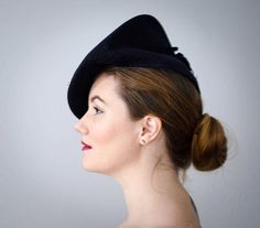 A dark navy blue beret, quite dramatic in silhouette, with a swirl and feather design on the crown. A blue velvet bow sits at the back.  Size: 22  Condition: Very good; the silk cording that surrounds the wool feather has worn in some spots.