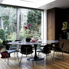 Dark oval tulip table and dark chairs, on a light wooden floor. Mesa Saarinen Oval, Saarinen Table, Eero Saarinen, Dining Room Sets, Dining Room Design, Dining Room Furniture, Dark Furniture, Tulip Dining Table, Dining Chairs