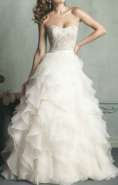 Featuring a strapless beaded bodice, this highlight of this strapless gown is the ruffled organza sk
