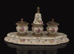 Bonita escribania realizada en porcelana policromada con motivos florales, compuesta por tres tinteros apoyados sobre base. Medidas: 26x14cm.