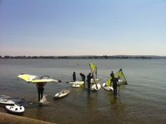 Poole Windsurfing students helping to get the kit ready in the shallows of Poole Harbour. #poolewindsurfing #windsurfschool #pooleharbour