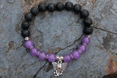 What you see is what you get - this is the only one of this bracelet I will make! Get it before its gone! - 8mm purple alexandrite stone beads. - 8mm black lava stone beads. - Silver tone elephant face charm and accents. - 6.5 Inches un-stretched (approximately). This bracelet best fits people with a medium frame. - Ships from Canada.  Such a cute elephant - perfect for any animal lover! Lovely purple beads stand out next to black lava stone - which is a natural diffuser. This bracelet…