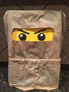 Ninjago Valentine's Day Mailbox: Draw eyes on yellow card stock and affix to shoe box. Wrap shoe box in cloth bag (mine was the wrapping from a sheet set). Cut bottom of bag to use as mask. Spray with gold spray paint for Golden Ninja. When dry, cut holes for eyes.