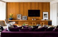 """Com acabamento de freijó, o móvel da TV, executado pela Marcenaria da Projearte, integra a parede revestida da mesma madeira neste living. """"Optei pelo painel de madeira natural, que veste a sala e a torna aconchegante"""", explica a arquiteta Vanessa Féres"""