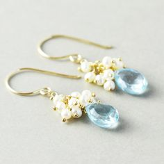 Gold filled earrings featuring 10mm faceted blue topaz drops handpicked to match as perfect as possible. They sway below a cluster of petite white