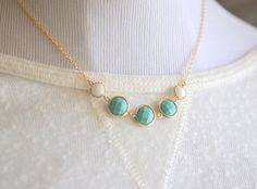 This necklace is very elegant simple and yet also has a pop of color with the framed stones in turquoise and white. Simple, awesome, and very