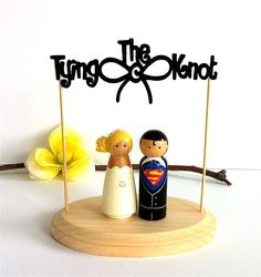 SUPERMAN  Wedding Cake Topper Clark Kent and Lois Lane with Tying The Knot Wood Stand Wedding Cake Topper Superhero Cake Topper Toppers. $102.00, via Etsy.