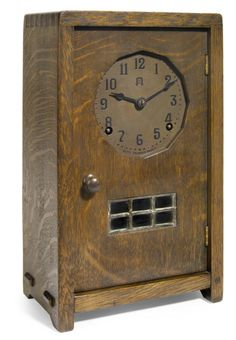 A Gustav Stickley oak and copper mantel clock  circa 1900, movement by Seth Thomas  dial stamped with Gustav Stickley logo and SETH THOMAS MOVT.