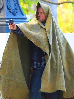Under cover: Charlie pointed a gun while having heavy fabric draped over him
