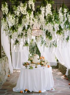 Chandelier glistens amidst a whimsical wisteria creation by Celadon Celery // Archive Rentals // #florals #cakestand #vintagerentals