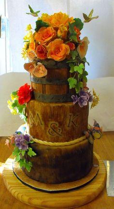 wood textured fondant covered wedding cake with sugar flowers, hummingbirds and butterflies. Vanilla cake with white chocolate fondant, dark chocolate ganache undercoat,  Swiss meringue buttercream in fig, lemon curd and chocolate hazelnut.