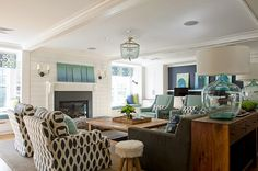 Olson Lewis Architects, turquoise and navy coastal living room with bead light, slate fireplace, glass lamps, and custom upholstry